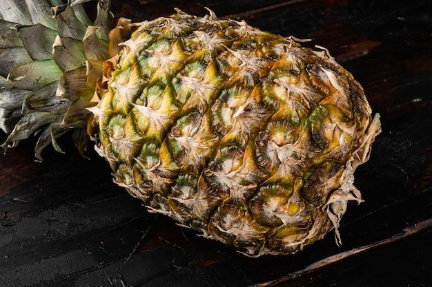 Ensemble d'ananas ou d'ananas jaunes, sur le vieux fond de table en bois foncé