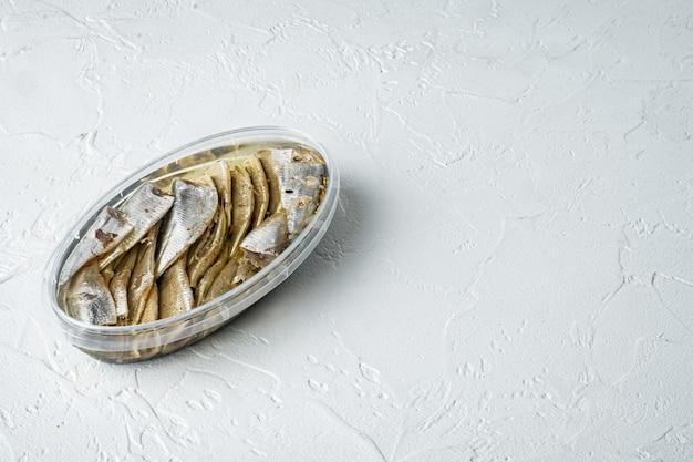 Ensemble d'anchois en conserve, dans un récipient en plastique, sur blanc