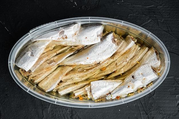 Ensemble d'anchois en conserve, dans un récipient en plastique, sur fond noir, vue de dessus à plat
