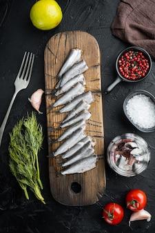 Ensemble d'anchois en conserve, sur une planche à découper en bois, sur fond noir