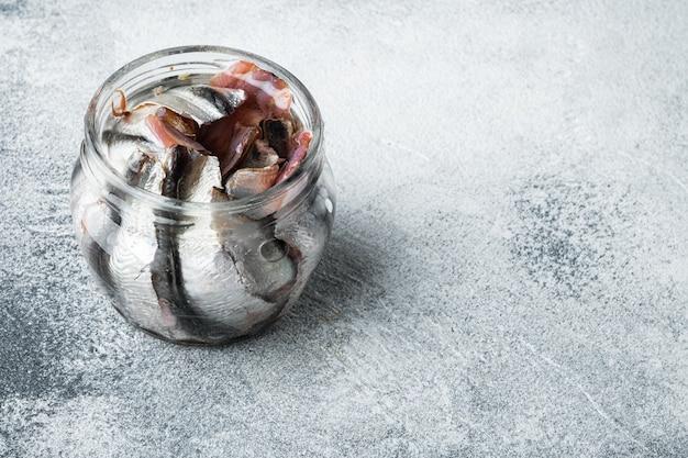 Ensemble d'anchois mariné, en bocal en verre, sur fond gris