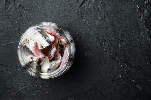 Ensemble d'anchois mariné, en bocal en verre, sur fond noir