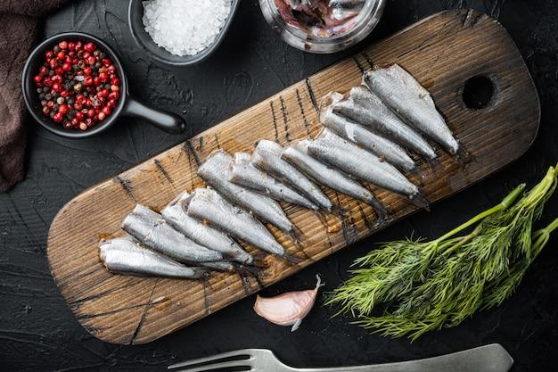 Ensemble d'anchois marinés, sur une planche à découper en bois, sur fond noir