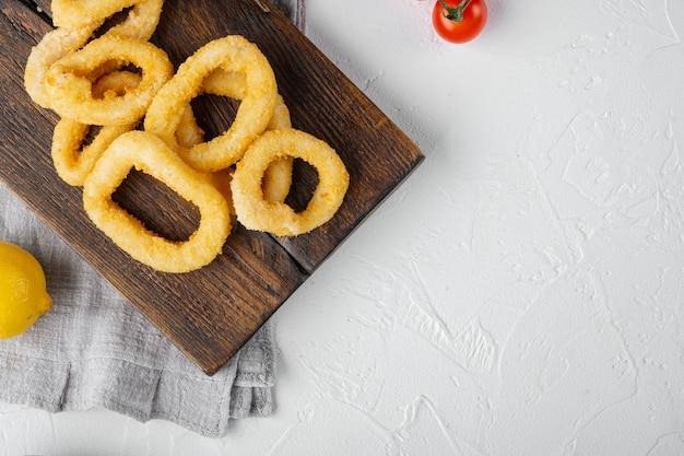 Ensemble d'anneaux de calamars panés au four, sur un plateau de service, sur fond de table en pierre blanche, vue de dessus à plat