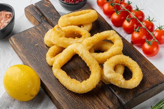 Ensemble d'anneaux de calamars panés cuits au four, sur une planche de service, sur fond de table en pierre blanche