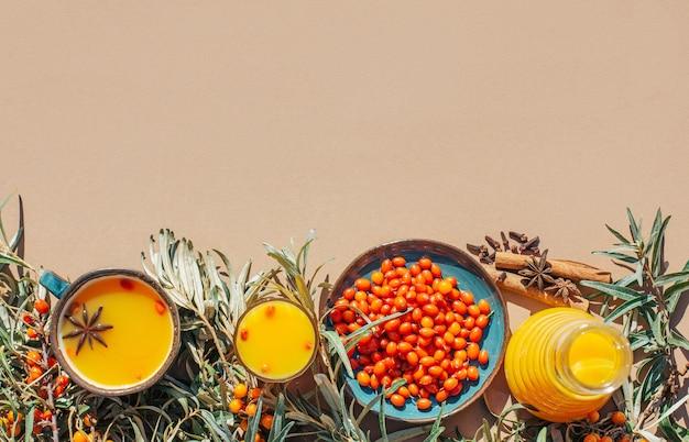 Ensemble anti-froid de thé d'argousier miel citron et gingembre sur fond marron clair antioxydant