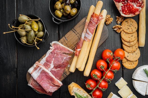 Ensemble d'antipasti italien classique, sur table en bois noir, mise à plat