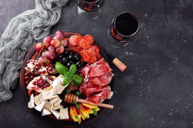 Un ensemble d'apéritifs pour le vin, le jamon, le pepperoni, le fromage, les raisins, la pêche et les olives sur une vue de dessus de planche de bois.
