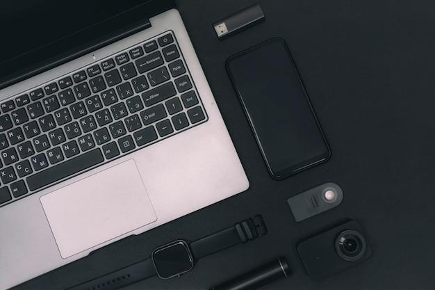 Ensemble d'appareils multimédias. ordinateur portable avec une caméra d'action, un smartphone, une montre intelligente et une banque d'alimentation avec clé usb sur fond noir.