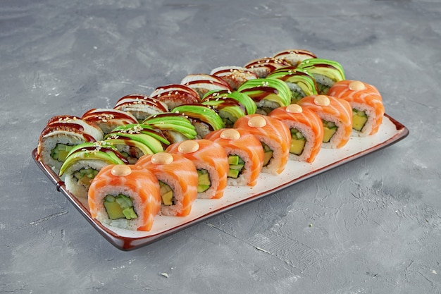 Ensemble appétissant de rouleaux de sushi dragon avec saumon, avocat et anguille dans une assiette blanche sur fond gris