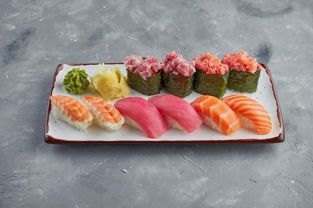 Ensemble appétissant de sushis et gunkans avec saumon, thon, krevekta et anguille, sauce épicée dans une assiette blanche sur fond gris