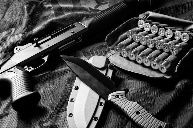 Ensemble d'armes d'un combattant d'une unité spéciale. fusil de chasse, cartouches, couteau. vue de dessus. technique mixte
