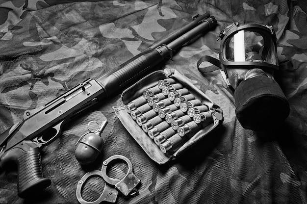 Ensemble d'armes d'un combattant d'une unité spéciale. fusil de chasse, munitions, grenade, menottes et masque à gaz. vue de dessus. technique mixte