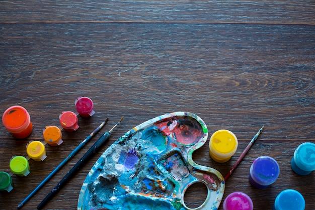 Ensemble d'art, palette, peinture, pinceaux sur fond en bois.