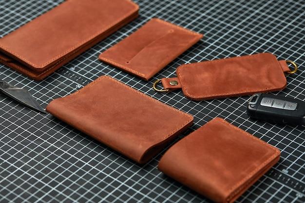 Ensemble d'articles en cuir faits à la main, anneaux porte-clés, portefeuille, sac à main, bloc-notes, manuel. maroquinerie artisanale, gros plan.