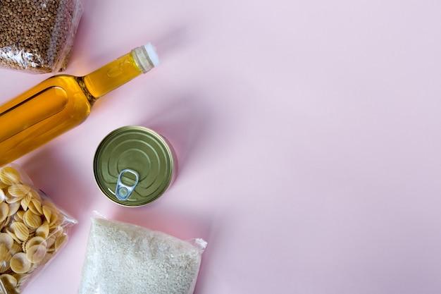 Ensemble d'articles d'épicerie en ligne de pâtes, huile, céréales à plat sur rose