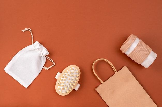Ensemble d'articles réutilisables pour un style de vie écologique. sac en coton et papier écologique, tasse à café, brosse à cheveux sur surface brune.