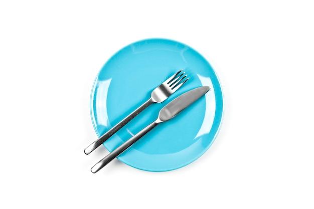 Ensemble d'assiette bleue vide, fourchette et couteau