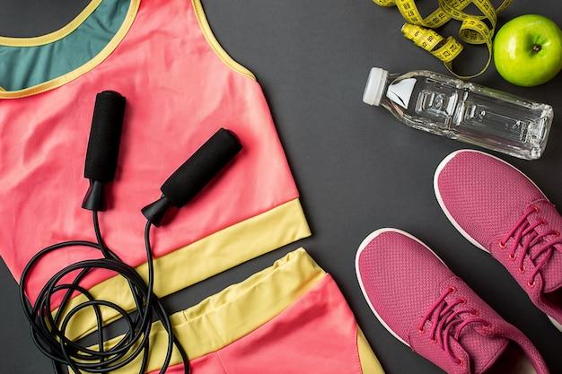 Ensemble d'athlète avec des vêtements féminins, des baskets et une bouteille d'eau sur fond gris. vue de dessus. espace de copie. nature morte. idéal pour blog sportif.