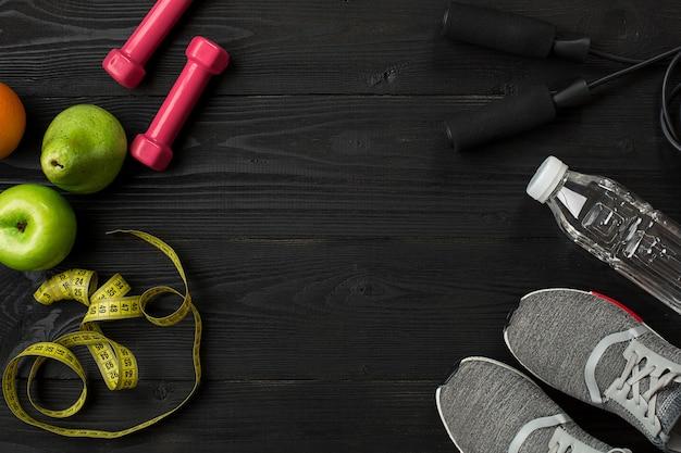 Ensemble de l'athlète avec des vêtements féminins, des baskets et une bouteille d'eau sur fond sombre. vue de dessus. espace de copie. nature morte. idéal pour blog sportif.