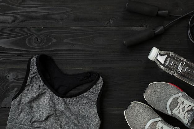 Ensemble de l'athlète avec des vêtements féminins et une bouteille d'eau sur fond sombre. vue de dessus. nature morte. espace de copie