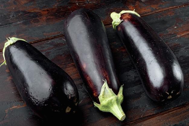 Ensemble d'aubergines violettes brutes fraîches, sur fond de table en bois ancien
