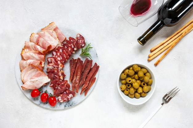 Ensemble de bacon fumé, salami et basturma servi avec olives marinées, tomates, vin et pain grissini