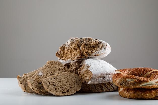 Ensemble de bagel turc et de pain de mie sur une surface blanche et grise. vue de côté.