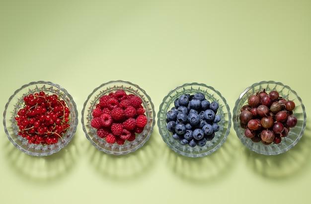 Ensemble de baies différentes dans des bols en verre sur fond vert avec des aliments sains d'ombres