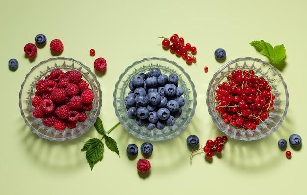 Ensemble de baies différentes dans des bols en verre sur fond vert avec concept de désintoxication et de vitamines des ombres