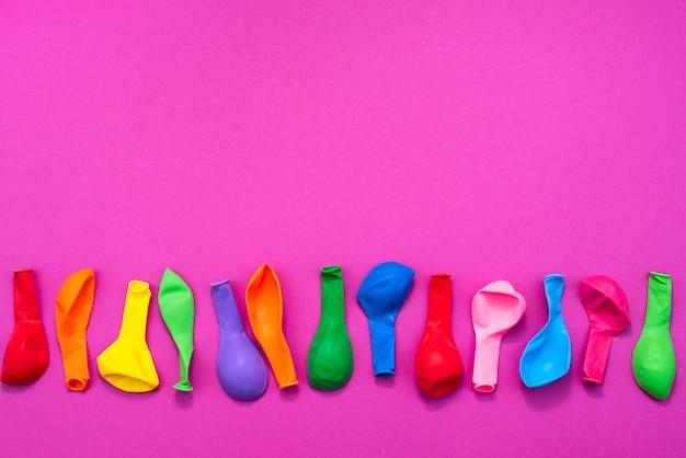 Ensemble de ballons colorés sur fond rose