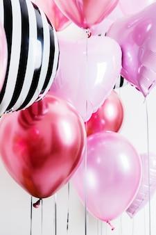 Ensemble de ballons en forme de coeur et rose rond et rayé sur fond clair avec espace copie.