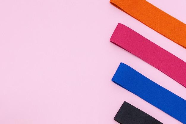 Un ensemble de bandes élastiques multicolores pour le fitness sur rose. mise à plat