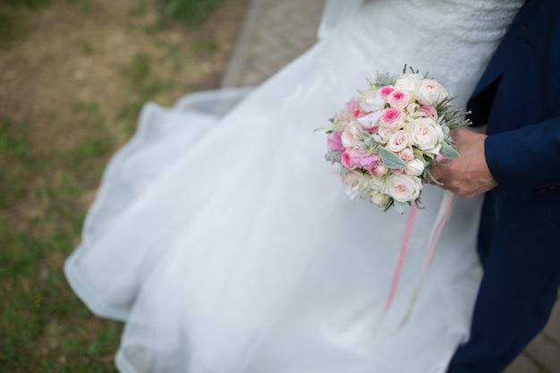 Ensemble. beau bouquet de mariage de différentes fleurs dans les mains de la mariée avec le marié. notion de mariée. bouquet de pivoines, roses, eustoma et feuilles vertes