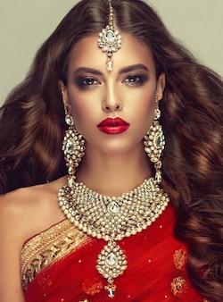 L'ensemble de bijoux chic est composé de grandes boucles d'oreilles, d'un collier lumineux et d'une parure de tête (tikka). cheveux parfaits, denses, ondulés, volant librement et maquillage de style
