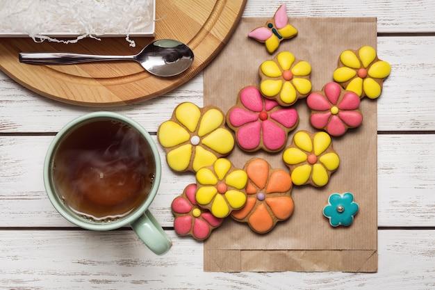 Ensemble de biscuits au gingembre sur sac en papier, cuillère à café et tasse de thé chaud.
