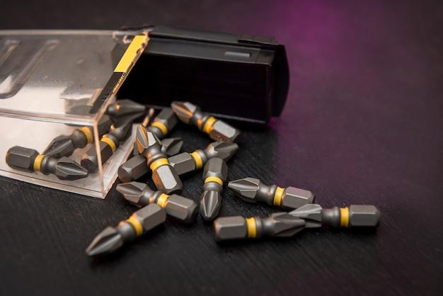 Ensemble de bits métalliques dispersés sur un tournevis de table noir. tout pour la réparation