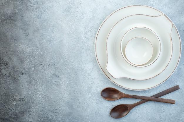 Ensemble blanc vide élégant pour le dîner et cuillères en bois sur une surface grise isolée avec espace libre