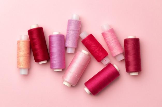 Ensemble de bobines de fils sur fond rose