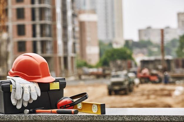 Ensemble de boîte à outils de vêtements de travail de sécurité et d'autres équipements professionnels se trouvant sur la surface en pierre contre
