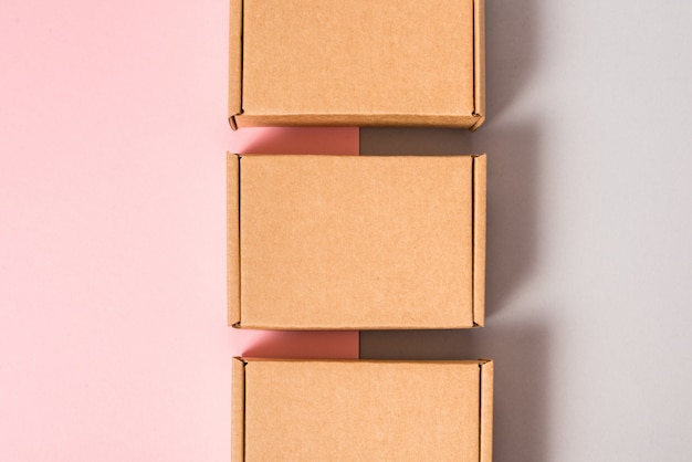 Ensemble de boîtes en carton marron sur fond rose et gris