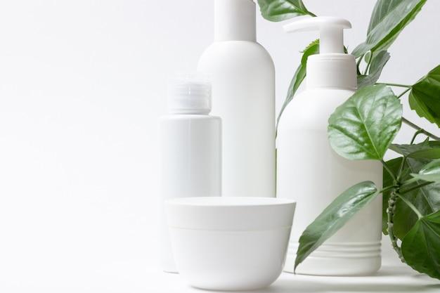 Ensemble de boîtes cosmétiques de produits cosmétiques biologiques pour les soins du visage et du corps sur fond blanc avec des feuilles vertes. crème, shampoing et lotion sur fond clair. mise en page, copiez l'espace.