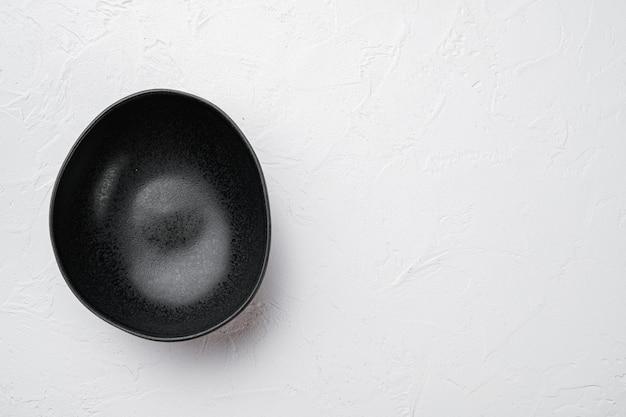 Ensemble de bols en poterie noire, avec espace de copie pour le texte ou la nourriture, avec espace de copie pour le texte ou la nourriture, vue de dessus à plat, sur fond de table en pierre blanche