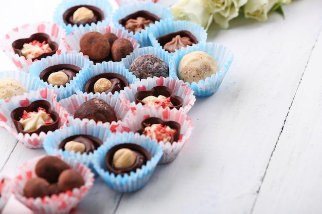 Ensemble de bonbons au chocolat avec des fleurs sur une surface en bois clair, gros plan