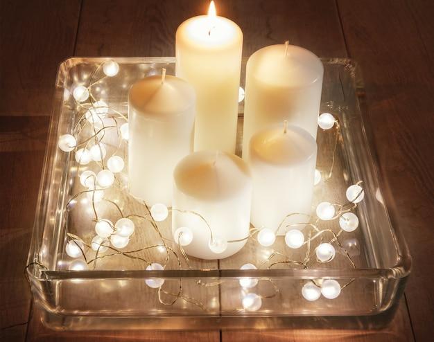 Ensemble de bougies blanches et guirlande dans un grand chandelier en verre sur fond en bois. le concept de noël, de l'avent, des vacances d'hiver.