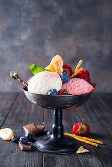 Ensemble de boules de crème glacée de différentes couleurs et saveurs avec des baies, chocolat