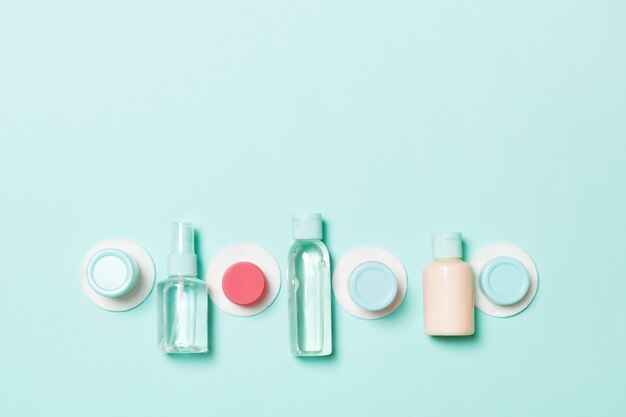 Ensemble de bouteilles cosmétiques de voyage sur fond bleu. mise à plat de pots de crème