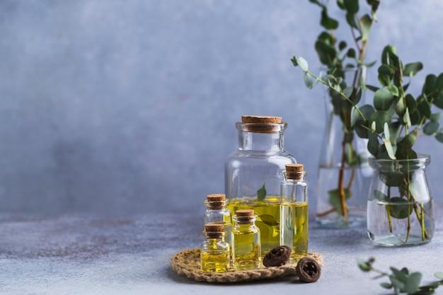 Ensemble de bouteilles en verre avec de l'huile essentielle d'eucalyptus sur des feuilles de table grises dans un vase