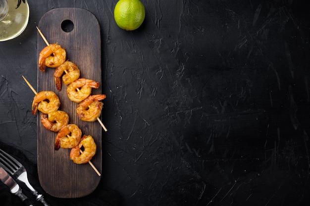 Ensemble de brochettes de crevettes, sur planche de service en bois, sur fond noir