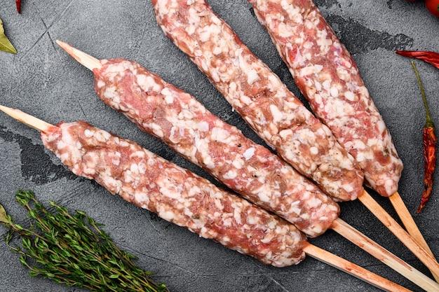 Ensemble de brochettes de mouton d'agneau hachées et en forme, avec des ingrédients de gril, sur fond de table en pierre grise, vue de dessus à plat